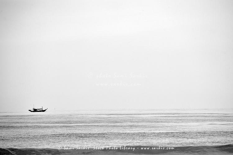 Remote Fishing boat over sea horizon, Lang Co Beach, Vietnam