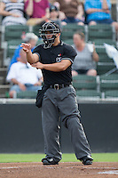 Home plate umpire Cody Clark makes a strike call during the South Atlantic League game between the Hagerstown Suns and the Kannapolis Intimidators at CMC-Northeast Stadium on August 16, 2015 in Kannapolis, North Carolina.  The Suns defeated the Intimidators 4-3 in game two of a double-header.  (Brian Westerholt/Four Seam Images)
