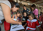 Raquel Fabre, a teacher with the Kapatiran-Kaunlaran Foundation (KKFI), helps children use glue and cotton balls to learn about the letter N in a KKFI-sponsored preschool in Pulilan, a village in Bulacan, Philippines.<br /> <br /> KKFI is supported by United Methodist Women.