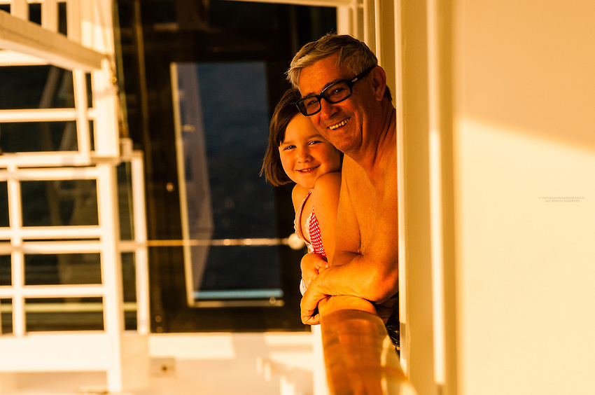"Passenger and his granddaughter Ryan looking off the verandah of their state room aboard the Disney ""Dream"" cruise ship on arrival at Disney's private island, Castaway Key, in the Bahamas."