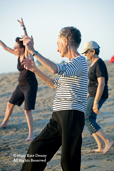 Three senior women move in exercise routine with arms bent upward on beach in Playa del Rey, California