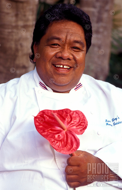 Local celebrity chef Sam Choy holding an anthurium