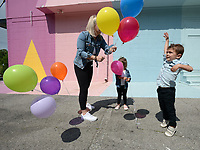 Roman Smolinski, 3, (right) leaps Thursday, May 21, 2020, as he and his twin sister, Charleston Smolinski are given balloons by their mother, Ally Smolinski of Rogers, while taking family photographs in front of the Maude Wall at Maude Boutique in Fayetteville. The clothing store invites patrons to use their multicolored back wall for photographs. Visit nwaonline.com/200522Daily/ for today's photo gallery.<br /> (NWA Democrat-Gazette/Andy Shupe)