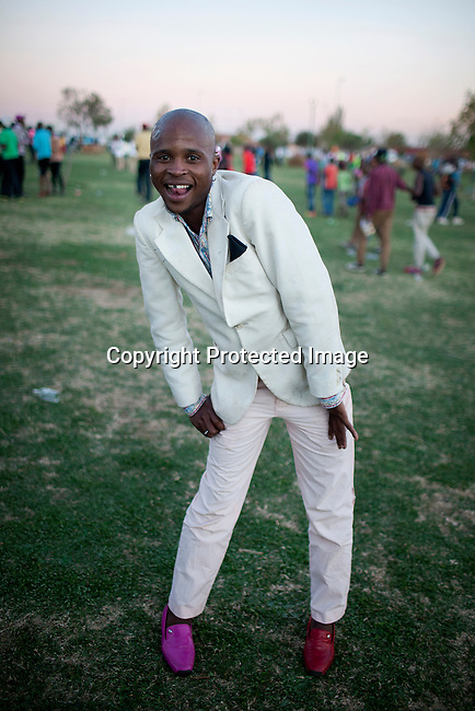 SOWETO, SOUTH AFRICA SEPTEMBER 29: An Izikhothane youth shows off his clothes and shoes on September 29, 2012 in Thokoza Park, Soweto, South Africa. Hundreds of Izikhothane kids gathered in Thokoza Park and moved on to other areas in Soweto, to show off their dance moves and play loud music. The Izikhothane bling kids are the new fears of residents and parents in the townships of Johannesburg. They buy (and sometimes burn and destroy) fancy brand clothes and shoes in Soweto. They also like to drink and display expensive bottles of alcohol. Many of these kids are desperate to get the latest clothes and the pressure is hard on their parents. (Photo by: Per-Anders Pettersson)