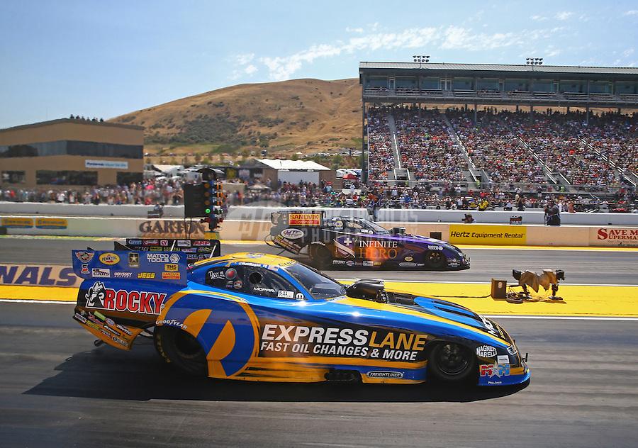 Aug 1, 2015; Sonoma, CA, USA; NHRA funny car driver Matt Hagan (near) races alongside Jack Beckman during qualifying for the Sonoma Nationals at Sonoma Raceway. Mandatory Credit: Mark J. Rebilas-