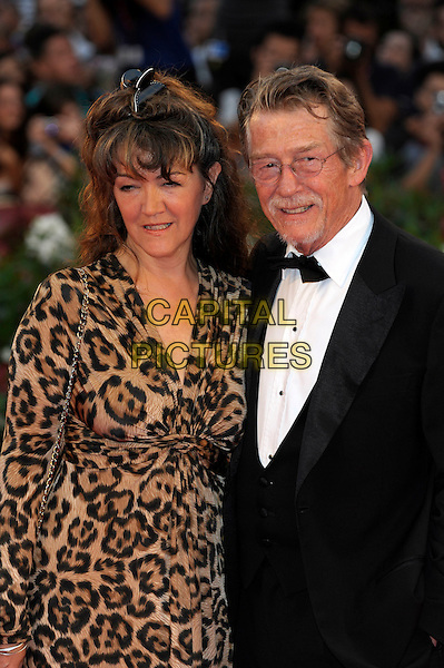 Anwen Rees Meyers & John Hurt.The 'Tinker, Tailor, Soldier, Spy' premiere at the Palazzo del Cinema during the 68th Venice Film Festival, Venice, Italy..September 5th, 2011.half length black tuxedo leopard print glasses goatee facial hair brown dress married husband wife .CAP/PL.©Phil Loftus/Capital Pictures.