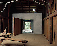 A massive pine door set in a large concrete block leads from the restored barn situated to one side of the house to the living areas beyond