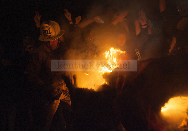 A firefighter puts out a burning couch fire as UK fans celebrate UK's win over Wisconsin in Lexington , Ky.,on Saturday, April 5, 2014. Photo by Michael Reaves | Staff