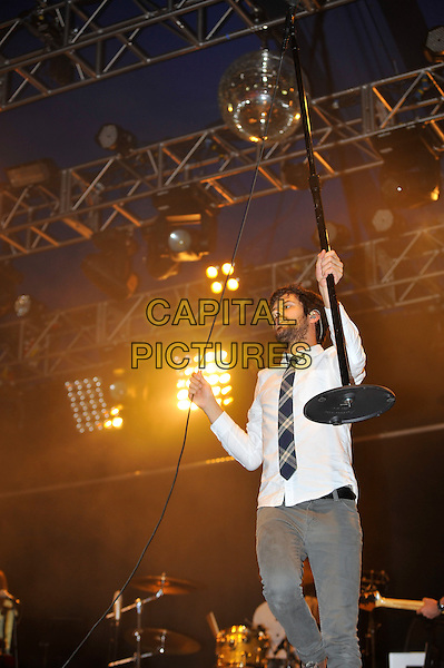 Michael Angelakos of Passion Pit.at Reading Festival, Reading, England, UK, 24th August 2012..music concert on stage live gig half length grey gray tie shirt shirt holding mic stand .CAP/MAR.© Martin Harris/Capital Pictures.