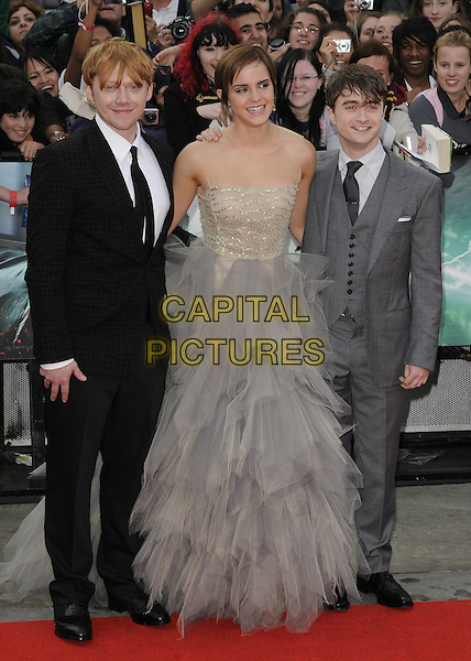 Rupert Grint, Emma Watson, Daniel Radcliffe.'Harry Potter and the Deathly Hallows - Part 2' world film premiere arrivals Trafalgar Square, London, England 7th July 2011.HP7 full length grey gray beige dress gown strapless sleeveless mesh tulle sheer beads beaded black suit.CAP/CAN.©Can Nguyen/Capital Pictures.