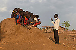 Ganun Butros Wadko talks with a group of children sitting on an anthill in the Doro Refugee Camp in Maban County, South Sudan. Doro is one of four camps in Maban which together shelter more than 130,000 refugees from the Blue Nile region of Sudan. Jesuit Refugee Service, with support from Misean Cara, provides educational and psychosocial services to both refugees and the host community. Wadko, a refugee himself, is supervisor of the JRS psychosocial team's home visits in the Doro Camp.