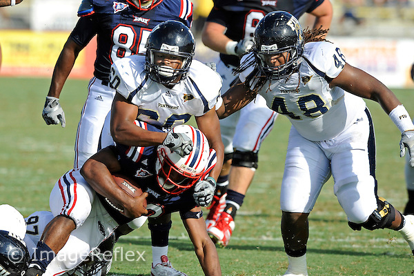 30 October 2010:  FIU linebacker Chris Edwards (60) tackles Florida Atlantic running back Alfred Morris (32) as FIU defensive tackle Kasey Smith (48) follows in pursuit as the Florida Atlantic University Owls defeated the FIU Golden Panthers, 21-9, at Lockhart Stadium in Fort Lauderdale, Florida.