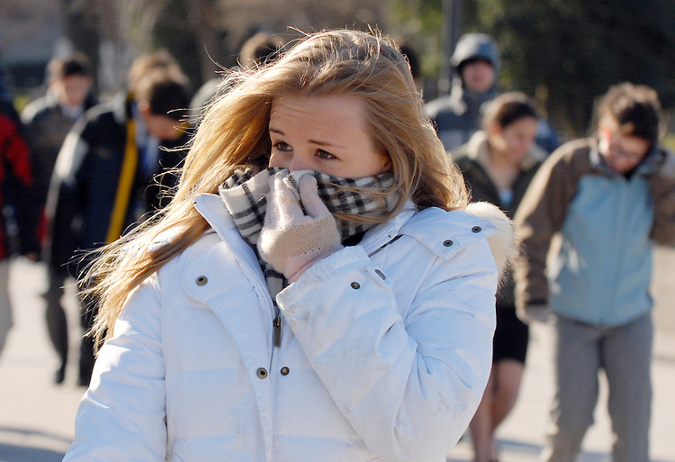 A student shields her face from the cold on the west front of the Capitol.