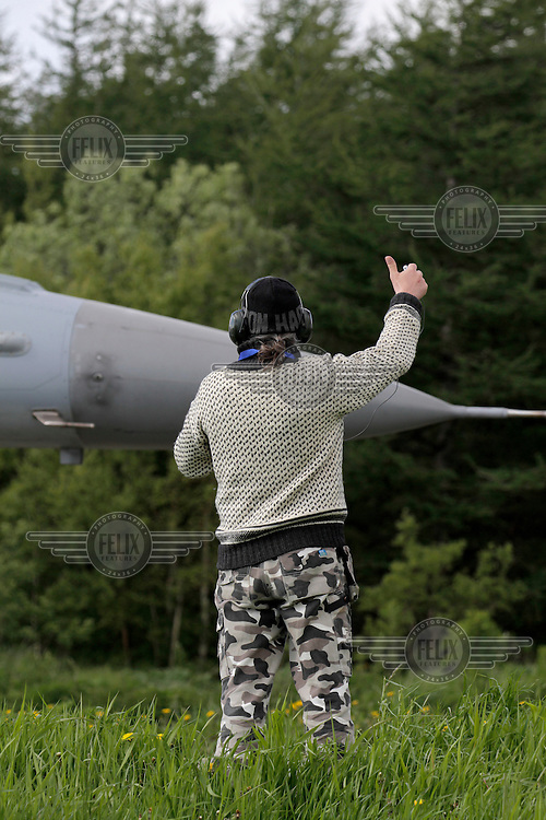 An airplane spotter signals to the pilot of a F-16 fighter plane. Nato Tiger Meet is an annual gathering of squadrons using the tiger as their mascot. While originally mostly a social event it is now a full military exercise. Tiger Meet 2012 was held at the Norwegian air base Ørlandet.