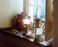 A paraffin lamp, earthenware pot and candlestick on a sunny window sill