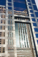 Dubai, United Arab Emirates. Reflections in the faade of modern glass clad building. Abu Dhabi Road..