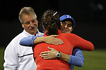22 November 2013: Duke assistant coach Carla Overbeck embraces Florida head coach Becky Burleigh (in orange) before the game as Duke head coach Robbie Church (in white) watches. The University of Florida Gators played the Duke University Blue Devils at Koskinen Stadium in Durham, NC in a 2013 NCAA Division I Women's Soccer Tournament Second Round match. Duke won the game 1-0.