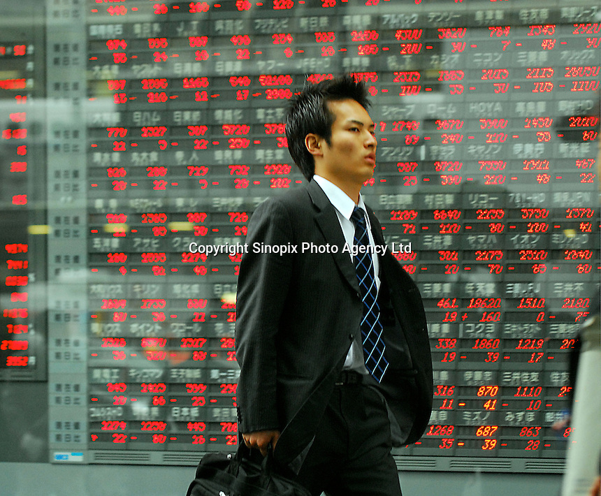 People pass in front of a Daiwa Securities centre that houses a board showing the latest financial results in Ginza, Tokyo. European stocks have fallen sharply in early Thursday trading, after the main Japanese index plummeted in Tokyo. With fears continuing that interest rate rises in the US will hit global growth, Japan's Nikkei ended the day down 463 points, or 3%, at 14,633. This was the Nikkei's biggest one-day drop in a year, and the first time it had fallen below 15,000 in 2006..