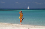 A young lady walks the West Bay beach on Roatan Island, Honduras
