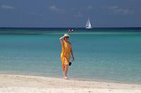 A young lady walks the West Bay beach on Roatan Island, Honduras