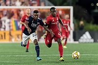 FOXBOROUGH, MA - ack201913: Richie Laryea #22 of Toronto FC brings the ball forward as DeJuan Jones #24 of New England Revolution defends during a game between Toronto FC and New England Revolution at Gillette Stadium on August 31, 2019 in Foxborough, Massachusetts.