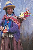 An old woman in Maras, near the Sacred Valley of the Incas in Peru, carrying flowers on her back and tomatoes in her hand.