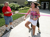 Elizabeth attains her lofty goal as she breaks a pink finish line tape while running out of On With Life, a brain injury rehabilitation center in Ankeny.  Her father, Mike, holds the line at left.