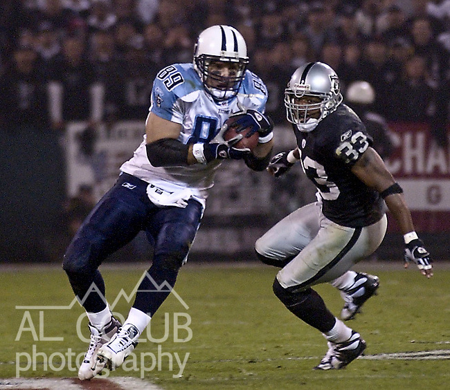 Tennessee Titans tight end Frank Wycheck (89) catches pass with Oakland Raiders defensive back Anthony Dorsett (33) close behind on Sunday, January 19, 2003, in Oakland, California. The Raiders defeated the Titans 41-24 in the conference championship game.