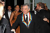 Washington, DC - December 5, 2009 -- Robert De Niro shakes hands with an unidentified person after he and his fellow 2009 Kennedy Center honorees posed for the formal group photo following the Artist's Dinner at the United States Department of State in Washington, D.C. on Saturday, December 5, 2009.  Also visible in the photo are his wife, Grace Hightower, left, and Sting, right..Credit: Ron Sachs - Pool via CNP