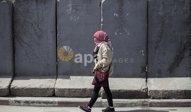 A Palestinian woman walks near the Israel's controversial separation barrier, during clashes following a rally ahead of International Woman's Day, at Qalandiya checkpoint near the West Bank city of Ramallah March 7, 2015. Photo by Shadi Hatem