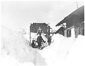Front view of Jordan spreader OU in snow at Cumbres station.  Two men are working the snow, one with shovel.<br /> D&amp;RGW  Cumbres, CO  2/1929