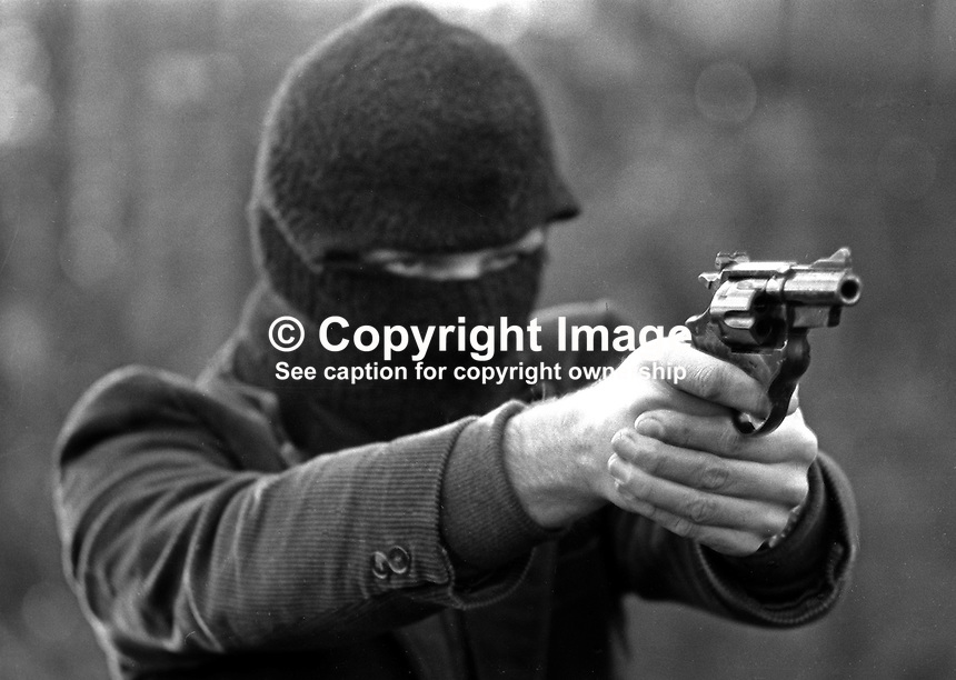Hooded man posing with .357 Magnum handgun in Thiepval Barracks, the British Army headquarters in N Ireland. The gun was recovered from the Provisional IRA by the security forces in N Ireland. It was discovered that this actual gun had been used in a murder bid on a senior legal figure in Belfast. The discovery of the weapon signalled a major escalation in the Provos' firepower. A further security force concern was that the gun had smuggled in from the USA were is was made under licence from Spanish company, AyA, aka Aguirre & Aranzabal, and reckoned to be more powerful than the Colt 45 revolver. It was popularly known as the Dirty Harry gun alluding to the Clint Eastwood film of that name  197512000753c...Copyright Image from Victor Patterson, 54 Dorchester Park, Belfast, United Kingdom, UK...For my Terms and Conditions of Use go to http://www.victorpatterson.com/Victor_Patterson/Terms_%26_Conditions.html