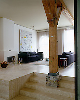 A substantial wooden column supports the ceiling of this open plan living room