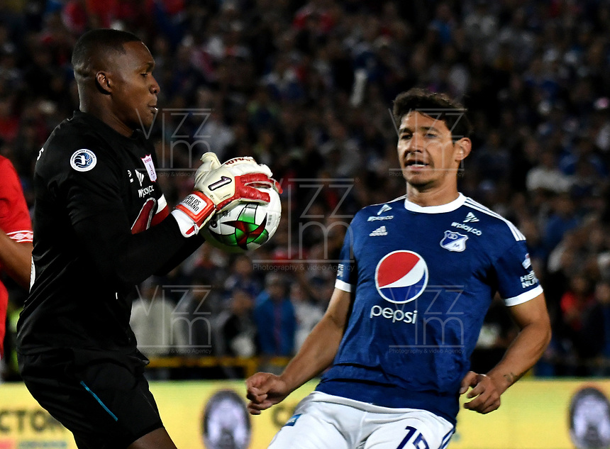 BOGOTÁ - COLOMBIA, 18-01-2019: Roberto Ovelar (Der.) jugador de Millonarios disputa el balón con Carlos Bejarano (Izq.) Guardavallas de América de Cali, durante partido entre Millonarios y América de Cali, por el Torneo Fox Sports 2019, jugado en el estadio Nemesio Camacho El Campin de la ciudad de Bogotá. / Roberto Ovelar (R) player of Millonarios vies for the ball with Carlos Bejarano (L) goalkeeper of America de Cali, during a match between Millonarios and America de Cali, for the Fox Sports Tournament 2019, played at the Nemesio Camacho El Campin stadium in the city of Bogota. Photo: VizzorImage / Luis Ramírez / Staff.