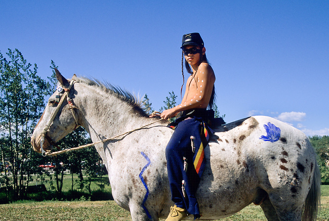 Blackfeet teenager dressed in mid 1800's regalia with cavalry hat sits bareback on an appaloosa horse in Browning Montana