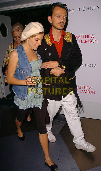 SIENNA MILLER & MATTHEW WILLIAMSON.Attends the Matthew Williamson Fragrance Launch Party, Fifth Floor Bar, Harvey Nichols, Knightsbridge, London, June 14th 2005..full length white cream beret hat denim waistcoat shirt glass drink.Ref: CAN.www.capitalpictures.com.sales@capitalpictures.com.©Can Nguyen/Capital Pictures