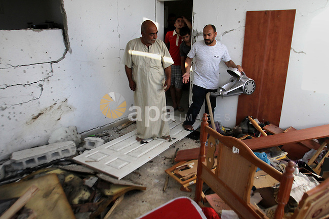 Palestinian men inspect the damage after their house was searched by Israeli forces on June 17, 2014 at the Balata refugee camp, close to the northern West Bank city of Nablus. Large numbers of Israeli soldiers raided the northern West Bank city of Nablus and its surroundings early 17 June 2014 in the search of three teenagers, three teenagers - Eyal Yifrah, 19, Gilad Shaar, 16, and Naftali Frenkel, 16 - missing since 08 JUne 2014, near the Gush Etzion settlement bloc, north of Hebron. Photo by Nedal Eshtayah