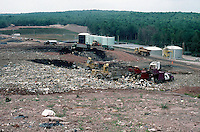 LANDFILL MANAGEMENT<br /> Overview of Layering<br />  Sullivan County, NY<br /> Landfill refuse is deposited in shallow layers, compacted, and covered within 24 hours with earth or other chemically inert material to form an effective seal. Mechanical equipment such as a bulldozer is used to grade, compact, and cover the refuse.