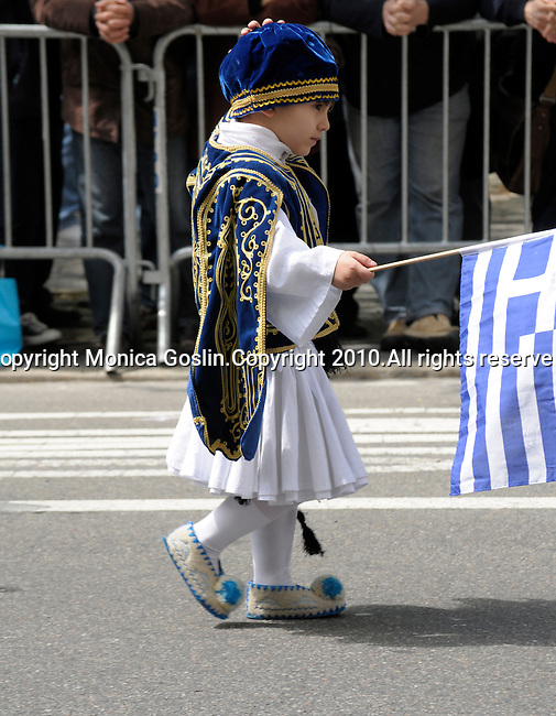 Greek Parade in New York City. A boy dressed in traditional clothing and holding a Greek flag, walking in the Greek Parade in New York City.