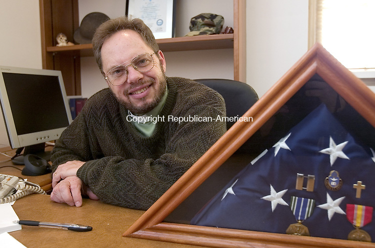 SEYMOUR, CT. 03 January 2008-010308SV03--The new pastor at the Seymour Congregational Church, Greg Dawson of Torrington, sits in his office at the church Thursday. Dawson sits with items from when he was an Army Chaplain. <br /> Steven Valenti Republican-American