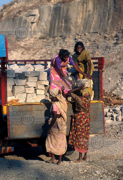 Dalit (Untouchable) women load stone blocks onto a lorry in a rural granite quarry which they now control.  Previously they were paid less than a dollar a day for their labour...