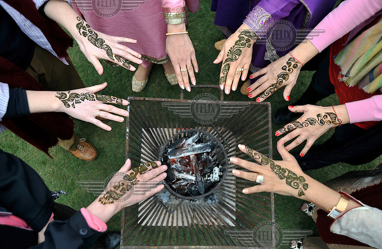 Guests of the bride dry their henna designs over a charcoal burner before the wedding of British/Punjabi couple Lindsay and Navneet Singh.
