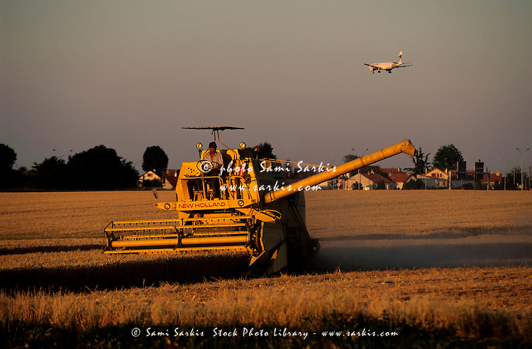 Man harvesting wheat from a field at sunset on a combine harvester, Orly, Paris, France.