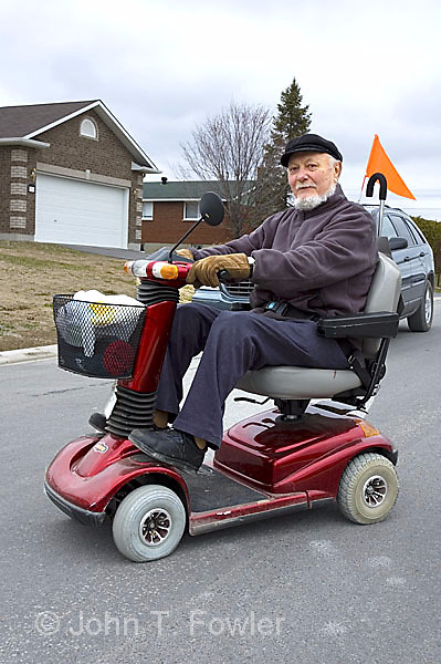 Elderly man using motorized scooter john fowler for Motorized scooters for elderly