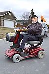 Elderly man using motorized scooter
