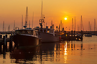 The sun rises over fishing boats and pleasure craft in Vineyard Haven Harbor in Tisbury, Massachusetts on Martha's Vineyard.