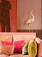 A sitting room, decorated in pastel colours, predominantly pink, with gilded mouldings. Textured cushions are scattered on a contemporary sofa designed by Henri Quinta.