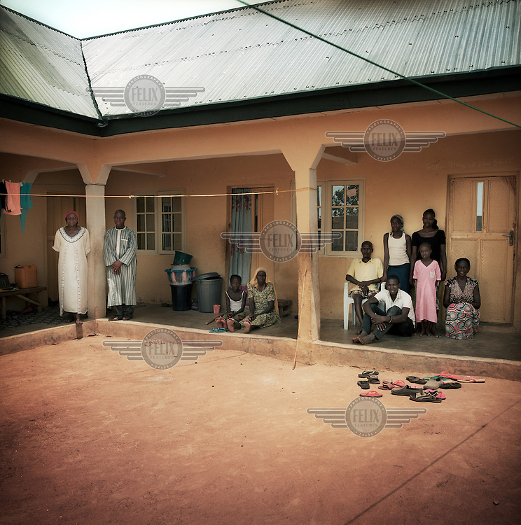 Three families from different backgrounds living together in the suburb of Yola town. They share a kitchen and bathroom in the courtyard. The room on the right is home to IDP family Samuel, his brother Vincent, aunt Esther and her children Imdaji (20), Chaem(14) and Lucy. The room in the middle belongs to IDPs Agnes (73) and Nancy (13) and the one on the left to Mrs Rose and Oliver who were born and raised in Yola. They already lived in their apartment when the IDPs came to join them. Oliver is honest about the new situation: 'I understand that many came to us to escape the violence. They are most welcome and I help them in every way I can. I gave all sorts of items to my neighbours. The only problem is, that their presence here also makes live more difficult for the hosts. Rents and food prices have gone up and the low wage jobs are being given to IDPs instead of our own people. So people who are from this area originally are unemployed. <br /> Oliver: 'I feel sorry for Samuel. He has been sick since he saw his father being killed. The doctors can't find what is causing this.