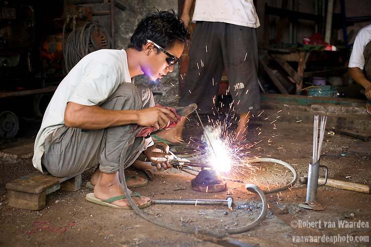 An Indonesian man welds a automotive part together for a bike in Lombok, Indonesia.