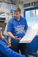 Two instructors having a discussion in the office, Able Skills, Dartford, Kent.